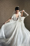 尝试在婚礼礼服的性感的肉欲的深色的新娘 免版税库存照片
