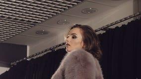 尝试在富有的皮大衣和摆在精品店的照相机的聪明的女孩 股票录像