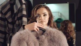 尝试在富有的皮大衣的聪明的女孩对在精品店的照相机 股票录像