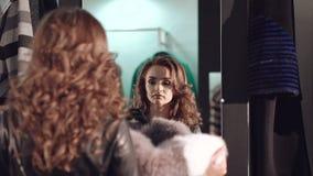 尝试在富有的皮大衣的聪明的女孩对在精品店的镜子 股票录像