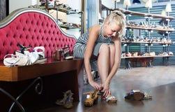 尝试在对的女孩在鞋店的凉鞋 免版税库存图片