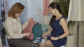 尝试在布料的年轻clother设计师妇女对她的客户在裁缝演播室 股票视频