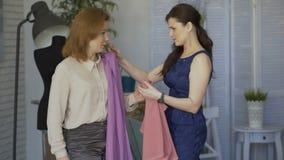 尝试在布料的年轻clother设计师妇女对她的客户在裁缝演播室 股票录像