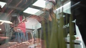 尝试在时髦的总体的一名时髦的行家妇女在商店 视图通过视窗 购物 股票视频