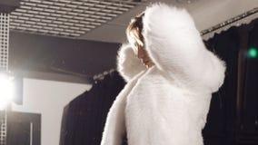 尝试在精品店的富有的白色皮大衣的俏丽的女孩 影视素材