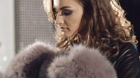 尝试在精品店的富有的皮大衣的聪明的女孩 股票视频