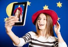尝试在红色帽子和做的年轻愉快的妇女 图库摄影