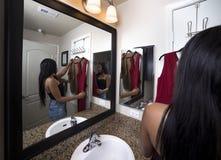 尝试在衣裳的妇女看镜子在卫生间里 库存照片