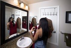 尝试在衣裳的妇女看镜子在卫生间里 免版税库存照片