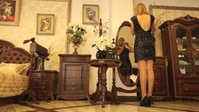 尝试在镜子前面的耳环的美丽的妇女 站立在镜子附近的美丽,典雅的女孩 股票视频