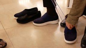 尝试在鞋店的新的黑运动鞋的妇女的行动 股票视频