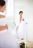 尝试她的礼服的年轻美丽的新娘 图库摄影