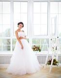 尝试她的礼服的年轻美丽的新娘 免版税图库摄影