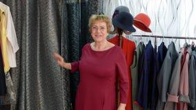 尝试新的礼服的愉快的年长妇女在时尚商店试衣间  影视素材