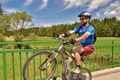 尝试有他的自行车的年轻人一个自行车前轮离地平衡特技 免版税图库摄影