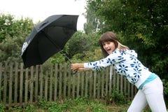 尝试的伞的女孩暂挂 免版税库存图片