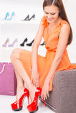 尝试红色鞋子的妇女坐在商店 免版税库存照片