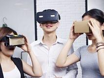 尝试虚拟现实风镜的年轻亚裔人民 库存图片