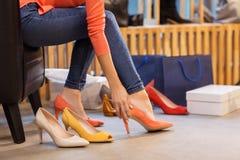 尝试高跟鞋的少妇在商店 免版税库存图片