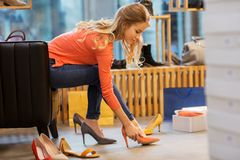 尝试高跟鞋的少妇在商店 免版税图库摄影