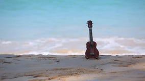 尤克里里琴、在海滩上把放的hawai仪器和蓝色海和波浪 股票视频
