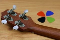 尤克里里琴头和五颜六色的吉他在木背景采摘 免版税库存照片