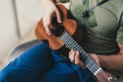 尤克里里琴比赛 弹一把小的吉他的一个人 执行者在尤克里里琴在家写音乐 免版税库存照片