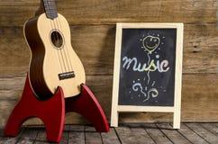 尤克里里琴吉他和黑板有在木背景写的词音乐的 免版税库存图片