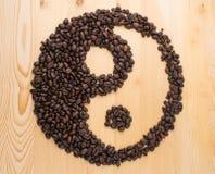 尹杨标志由咖啡豆制成在木桌 免版税库存图片