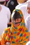 尼兹瓦,阿曼- 2012年2月3日:一名流浪的阿曼妇女的画象在尼兹瓦传统上穿戴了出席山羊市场 库存照片