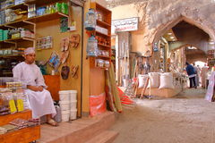 尼兹瓦,阿曼- 2012年2月2日:Souq在有一个阿曼人的尼兹瓦老镇在左边传统上穿戴了 免版税图库摄影