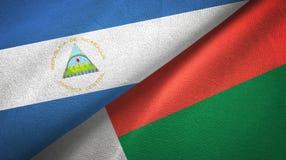 尼加拉瓜和马达加斯加两旗子纺织品布料,织品纹理 免版税库存照片