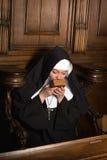尼姑亲吻的祈祷书 免版税库存图片