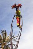 尼斯狂欢节,花`争斗 有小丑服装的一名杂技演员妇女在天空背景 免版税库存照片