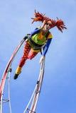 尼斯狂欢节,花`争斗 有小丑服装的一名杂技演员妇女在天空背景 库存图片