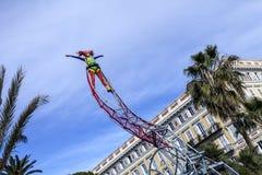 尼斯著名狂欢节,花`争斗 有小丑服装的一名杂技演员妇女在天空背景 免版税库存照片