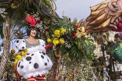 尼斯著名狂欢节,花`争斗 白色服装和黄色花的一名妇女 库存照片