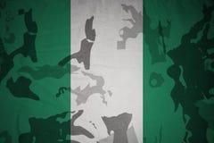 尼日利亚的旗子卡其色的纹理的 装甲攻击机体关闭概念标志绿色m4a1军用步枪s射击了数据条工作室作战u 库存照片