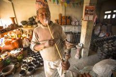 尼泊尔人在他的瓦器车间抽烟 库存照片