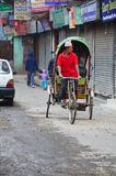 尼泊尔在thamel市场街道的人民乘坐的三轮车  免版税库存照片