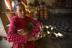 尼泊尔妇女在他的瓦器车间 库存照片