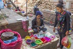 尼泊尔男孩为屠妖节节日卖在袋子的多彩多姿的油漆粉末在街道上 购物 图库摄影
