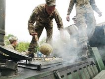 尼科波尔,乌克兰- 2019年5月:乌克兰军方烹调战士的粥并且对待人对它在游行以纪念 免版税库存图片