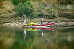 尼罗河,在卢克索附近,埃及, 2017年2月21日:在明亮的颜色绘的一条小船的,他们中的一个两位埃及渔夫sta 免版税图库摄影