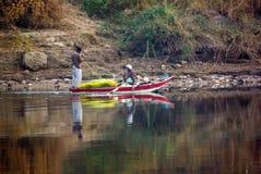 尼罗河,在卢克索附近,埃及, 2017年2月21日:在明亮的颜色绘的一条小船的,他们中的一个两位埃及渔夫sta 免版税库存照片