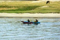 尼罗河,在阿斯旺附近, 2017年2月16日:一条小蓝色小船的两位渔夫特点尼罗河,一个荡桨和另一ha 库存图片