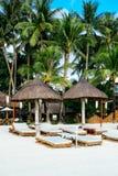 尼巴椰子小屋与竹sunbeds的太阳树荫在白色珊瑚沙子海滩 库存图片