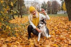 尾随使用黄色秋天的爱斯基摩和妇女 免版税图库摄影