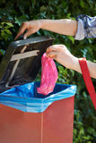 尾随把船尾袋子放的所有者入容器在步行上 库存图片
