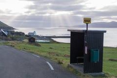 局部总线中止在Kirkjubøur,有Kirkjubø¸教会的法罗群岛在背景中 库存照片